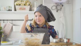 Girl baker mixes the mixture for cookies with a whisk. Close up Stock Image