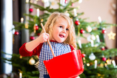 Girl baking cookies in front of Christmas tree Stock Photography