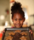 Girl Baking Gingerbread Cookies. Young girl holding a baking pan with gingerbread cookies prepared for baking Royalty Free Stock Images