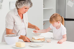 Girl baking with her grandmother at home Stock Photography