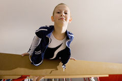 Girl (5-7) on balance beam in gymnasium, smiling, portrait, low angle view royalty free stock photos