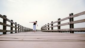 Girl balances along empty pier Stock Photo