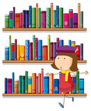 A girl balancing a book above her head in front of the bookshelv Royalty Free Stock Image