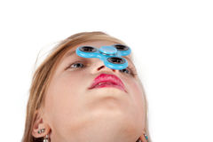 Girl balancing a fidget spinner on her nose.  Royalty Free Stock Images