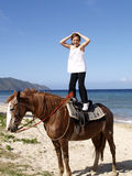 Girl balancing on horseback. Young girl stood balancing on horse on seaside beach, Cane Bay beach, Saint Croix, United States Virgin Islands Royalty Free Stock Photos