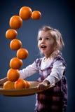 Girl balancing oranges Royalty Free Stock Images
