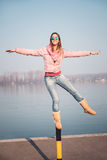 Girl balancing on parking pole Royalty Free Stock Photography
