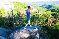 Girl is balancing on the stone. Royalty Free Stock Images