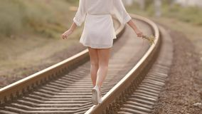 Woman balancing on train rail. Beauty, freedom, summer travel concept. stock video footage