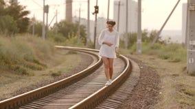 Woman balancing on train rail. Beauty, freedom, summer travel concept. stock video