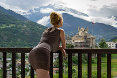 Girl on balcony. A beautiful girl resting on the balcony of the hotel watching a medieval mountain castle Stock Image