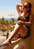 Girl on a balcony. Girl in sun glasses on a balcony on a background a sea and palms Stock Photography