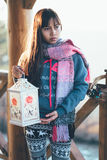 Girl on balcony holding candle lantern. In cold sunny weather Royalty Free Stock Photography