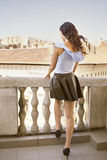 Girl on balcony. Looking over the roof-tops, vertical rear view Stock Photography