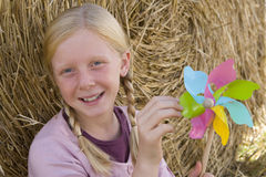 Girl (11-13) by bale of hay with pinwheel, smiling, portrait Stock Photo