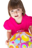 Girl with ball. Three years old girl, playing with a colored ball. Shot in the studio Stock Photo