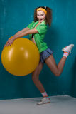 Girl with ball. Funny young girl with yellow fitball is smiling Stock Photos