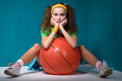 Girl with ball. Funny young girl with orange fitball is sitting Stock Photography