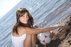 Girl with a ball on beach Stock Photos