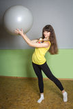 Girl with the ball doing exercises in the gym. Beautiful girl holding a large ball Royalty Free Stock Photography