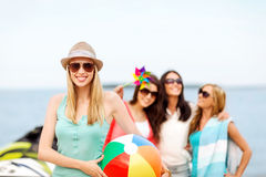 Girl with ball and friends on the beach Stock Image