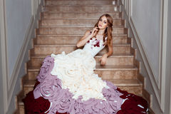 Girl in a ball gown lying on the steps. Royalty Free Stock Images