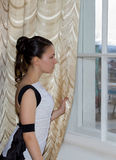 A girl in a ball gown standing by the window Royalty Free Stock Image