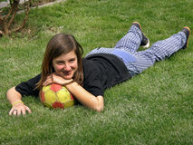 Girl with ball on green grass. Cute girl lying with the ball on the green grass. Vertical color photo royalty free stock image