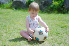 Girl with ball on lawn. A 1 year old girl playing with a football on a lawn Royalty Free Stock Images