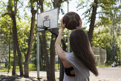 Girl with ball. Girl playing with a ball on the basketball court Stock Images
