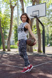 Girl with ball. Girl playing with a ball on the basketball court Stock Photos