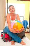 Girl with ball sitting on a suitcase and dreams Stock Photo
