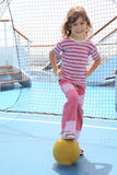 Girl with ball standing near football goal Stock Photo