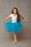 Girl ballerina in a blue tutu standing in dancing pose royalty free stock photo