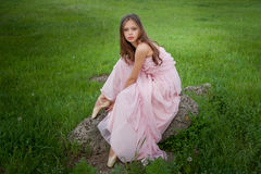 Girl ballerina in pointe sitting in a long dress on a stone amon. G the field Royalty Free Stock Image
