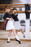 Girl at ballet barre. Ballet pas. Right profile. Reflection in mirror Royalty Free Stock Images