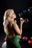 Girl with ballons and bubbles. On black background Stock Photos