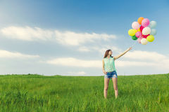 Girl with Ballons. Young beautiful woman with colorful balloons on a green meadow royalty free stock photography