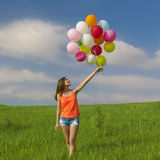 Girl with Ballons. Young beautiful woman having fun with balloons on a green meadow royalty free stock images
