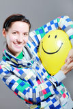 Girl with a balloon. Girl with a yellow smiley balloon against grey background Royalty Free Stock Photos
