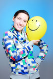 Girl with a balloon. Girl with a yellow smiley balloon against blue Royalty Free Stock Photos