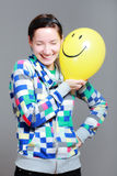 Girl with a balloon. Girl with a yellow smiley balloon against grey background Stock Photography
