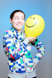 Girl with a balloon. Girl with a yellow smiley balloon against blue Royalty Free Stock Photo