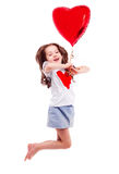 Girl with a balloon. Cute six year old girl  with a big red heart-shaped balloon, isolated against white background Stock Images