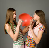 Girl and balloon. The girl pierces a pin a balloon (high speed photography royalty free stock photography