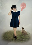 Girl, balloon and cat. Young girl with mischievous look in a dark dress with white collar, with a balloon on the field and the cat Stock Photo
