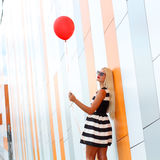 Girl with balloon. Happy young beautiful woman standing with colorful latex balloon. On the background an orange colored wall. Outdoors, lifestyle Stock Photos