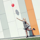 Girl with balloon. Happy young beautiful woman standing with colorful latex balloon. On the background an orange colored wall. Outdoors, lifestyle Stock Images