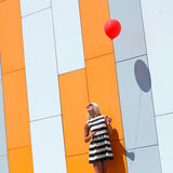 Girl with balloon. Happy young beautiful woman standing with colorful latex balloon. On the background an orange colored wall. Outdoors, lifestyle Royalty Free Stock Photo