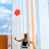 Girl with balloon. Happy young beautiful woman standing with colorful latex balloon. On the background an orange colored wall. Outdoors, lifestyle Royalty Free Stock Photos